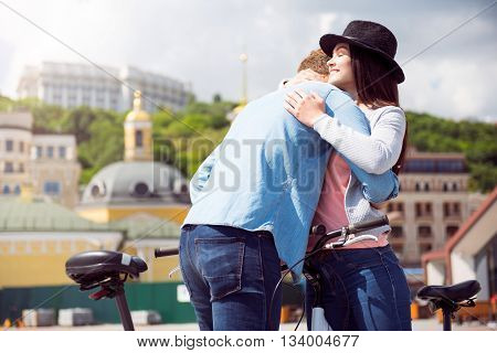 Moment to remember. Smiling satisfied young woman with closed eyes hugging a man while standing with bicycles