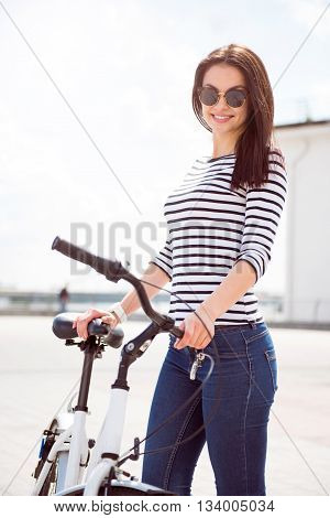 Enjoying the day. Gorgeous young woman with sunglasses standing on the quay near the bike