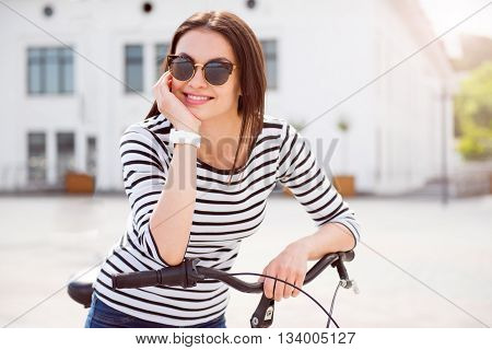 Some relax. Confident young woman with sunglasses holding a head with his hand on the handle bar while sitting on the bike