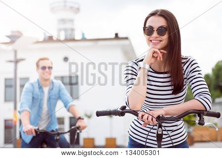 Relax. Confident young woman with sunglasses holding posing her arm on the handle bar of a bicycle with a man on the background