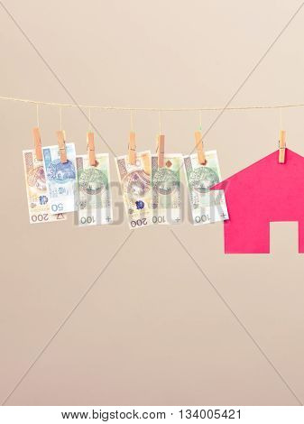 Red house with banknotes cash hang on laundry line. Selling and buying home concept.