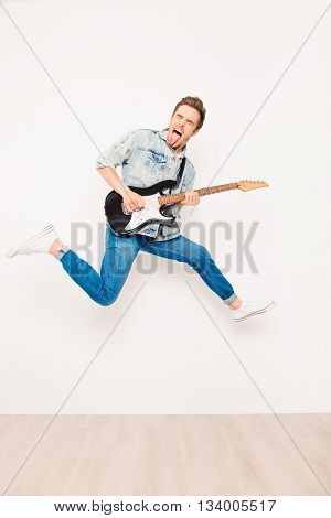 Young rocker playing on electro guitar, showing tongue  and jumping