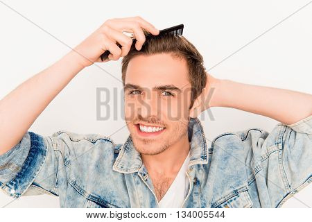 Handsome cheerful young guy doing modern hairstyle