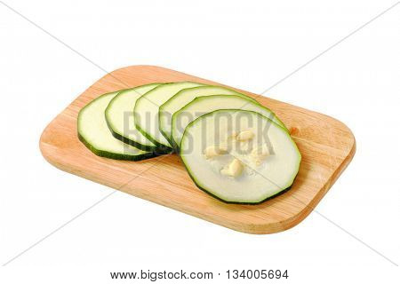 sliced zucchini on cutting board isolated on white