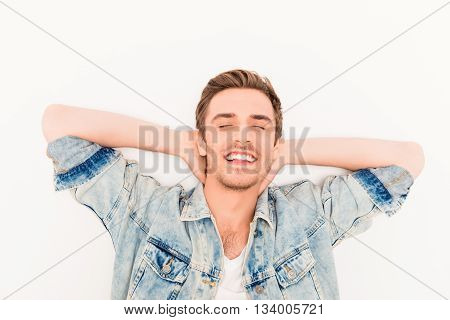 Young relaxed man with closed eyes touching neck and dreaming