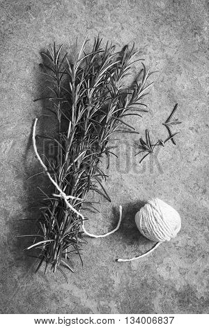 Bundle of fresh rosemary (lat. Rosmarinus officinalis) branches with a ball of yarn photographed overhead on slate with natural light (Digitally Altered: Monochrome Image)