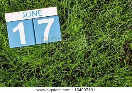 June 17th. Image of june 17 wooden color calendar on greengrass lawn background. Summer day, empty space for text.