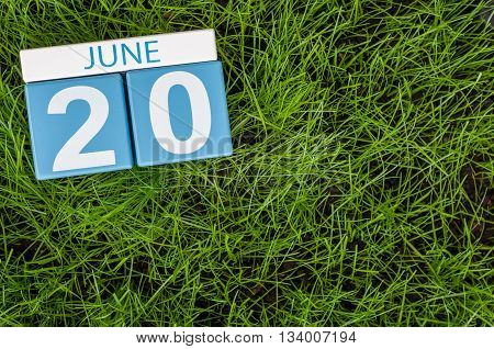 June 20th. Image of june 20 wooden color calendar on greengrass lawn background. Summer day, empty space for text.