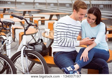 Look here. Handsome smiling guy and pleasant woman looking at the smartphone while sitting at the table and using earphones