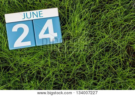 June 24th. Image of june 24 wooden color calendar on greengrass lawn background. Summer day, empty space for text.