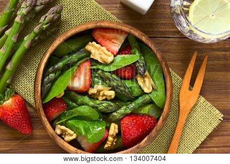 Fresh strawberry green asparagus baby spinach and walnut salad served in wooden bowl photographed overhead on dark wood with natural light (Selective Focus Focus on the top of the salad)