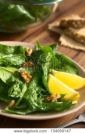 Fresh spinach and walnut salad with lemon wedges on the side served on plate photographed with natural light (Selective Focus Focus one third into the salad)