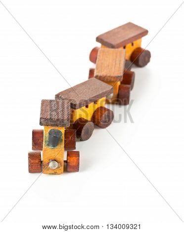 Old used wooden toy train with locomotive and wagons over white background