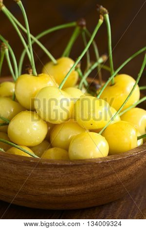Ripe yellow or Rainier cherry in wooden bowl photographed with natural light (Selective Focus Focus one third into the cherries)