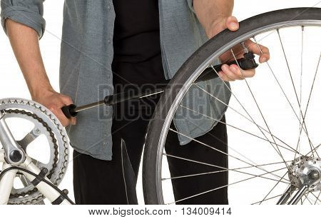 Man refilling front tire on a bicycle - bicycle service concept