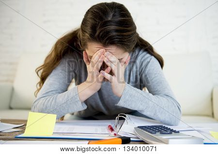 young attractive and desperate woman suffering stress doing domestic accounting paperwork bills and invoices worried and stressed at home sofa couch with bank folders and receipts