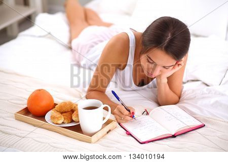 Young beautiful woman lying in bed writing a diary.