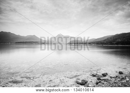 Cloudy Sunset At Mountain Lake. Stony Beach And Dark Mountains