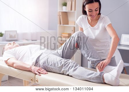 Exercise. Cheerful male patient lying down with female smiling physiotherapist performing some stretch exercises on mans leg
