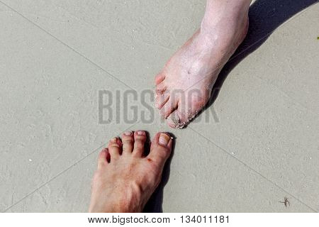 Feet Of Woman And Man Touching At The Beach