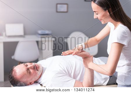 Healthy. Positive and cheerful female physiotherapist examining a man's hand in the medical office