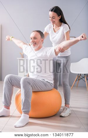 Rehabilitation praxis. Cheerful and happy male patient sitting on gym ball and smiling female physiotherapist performing some stretching exercises