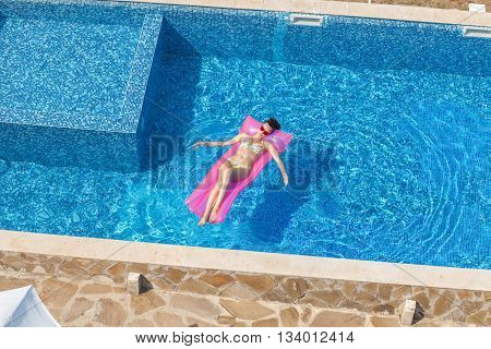 Young Sexy Brunette Woman Relaxing On Inflatable Mattress In Pool