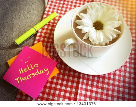 coffee cup on table with white daisy and words Hello Thursday vintage style