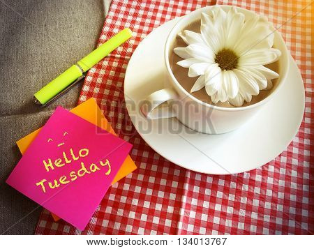 coffee cup on table with white daisy and words Hello Tuesday vintage style