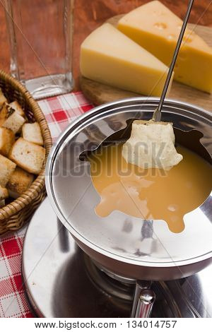 Cheese fondue - piece of bread (croutons) in a liquid cheese