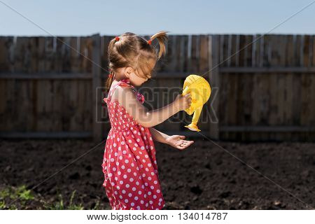 Little girl in a red spotted dress and hat with a yellow toy watering-can in the garden. The day is sunny and the shadow are deep.