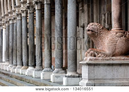 The columns of the Cremona's cathedral narthex stand on two lions in Verona marble. The left one is holding a dragon symbol of Evil in his paws.