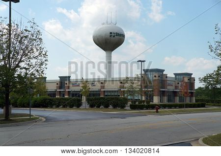 SHOREWOOD, ILLINOIS / UNITED STATES - AUGUST 16, 2015: The Shorewood Water Tower towers above the McColly Real Estate Office in Shorewood.