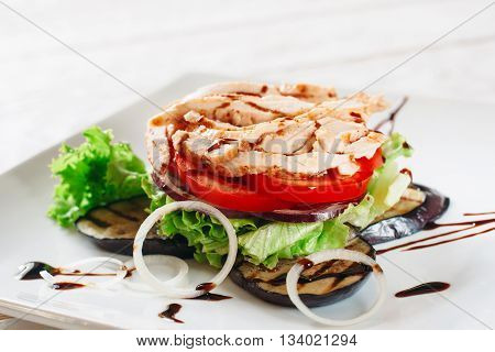 Chicken with grilled eggplant and tomato layered. Close-up of portion of layered meal of fried chicken, tomato, onion, lettuce and grilled eggplant, decorated with chocolate sauce