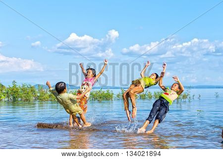 Dong Nai, Vietnam - November 15th, 2015: Children  jumping in lake afternoon with movements, flying directly into water exciting games childhood innocence rural areas in Dong Nai, Vietnam