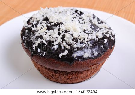 Homemade delicious fresh baked chocolate muffins with desiccated coconut lying on white plate