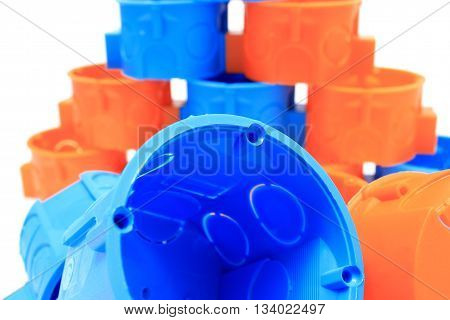 Blue and orange plastic electrical boxes on white background components for use in electrical installations accessories for engineering jobs