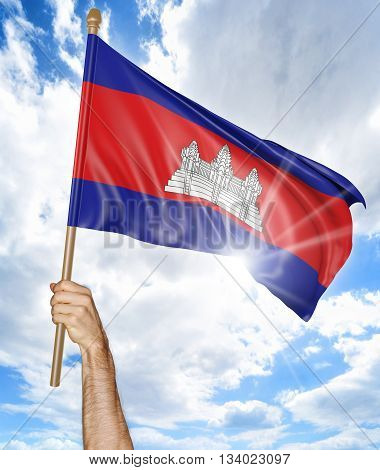 Person's hand holding the Cambodian national flag and waving it in the sky, part 3D rendering