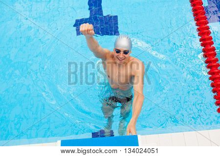 Winning Swimmer. Young muscular swimmer preparing. swimming pool