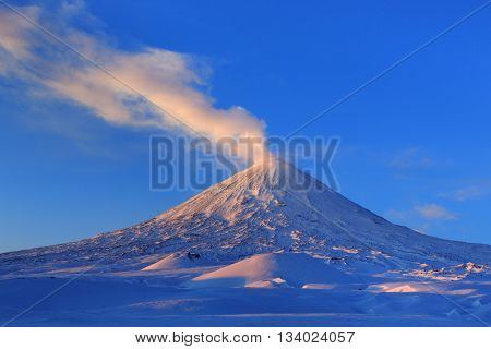 Beautiful winter volcanic landscape of Kamchatka Peninsula: view of eruption active Klyuchevskoy Volcano at sunrise. Eurasia Russia Far East Kamchatka Region Klyuchevskaya Group of Volcanoes.