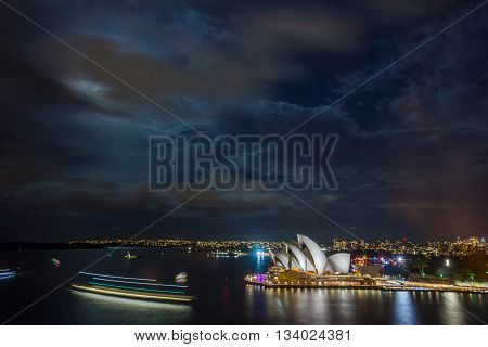 SYDNEY, AUSTRALIA - APRIL 22: View on illuminated Sydney Opera house at night with moon from the Harbour bridge. April 2016