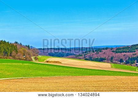 Landscape With Fields And A Village With Hills At The Horizon