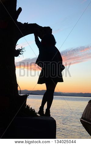silhouette of a woman looking out to sea, in late afternoon