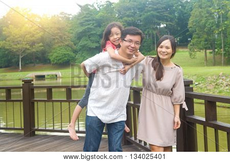 Happy Asian family outdoor. Father piggybacking his daughter walking in garden park with wife. Healthy lifestyle.