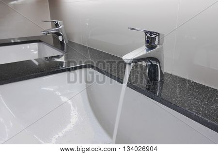 White Washbasins And Faucet On Granite Counter With Water Drop