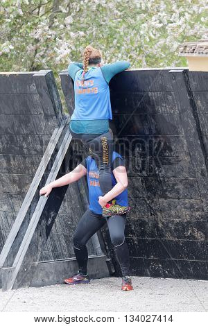 STOCKHOLM SWEDEN - MAY 14 2016: Two women helping eachother to climbing over a plank obstracle in the obstacle race Tough Viking Event in Sweden May 14 2016