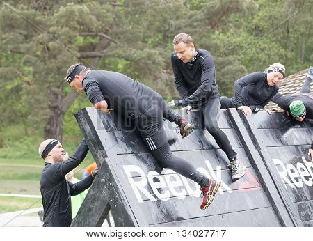 STOCKHOLM SWEDEN - MAY 14 2016: Women and men climbing over a plank obstracle in the obstacle race Tough Viking Event in Sweden May 14 2016
