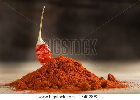 Red hot chili pepper and paprika powder over wooden background
