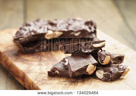 broken homemade bar of chocolate with cashew nuts reverse side, on wooden board shalow focus