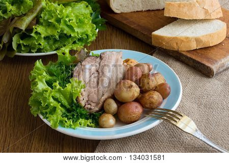 Crunchy roast Jacket Potatoes and baked pork. Serving in rustic style.